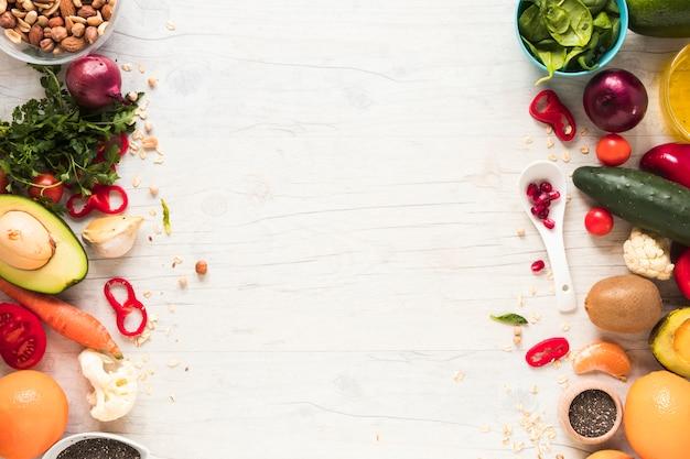 Свежие овощи; ингредиенты и фрукты на белом деревянном столе Premium Фотографии