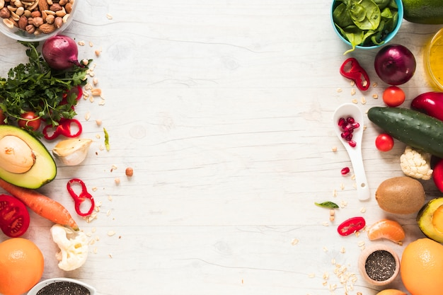 Fresh vegetables; ingredients and fruits arranged on white wooden table Free Photo