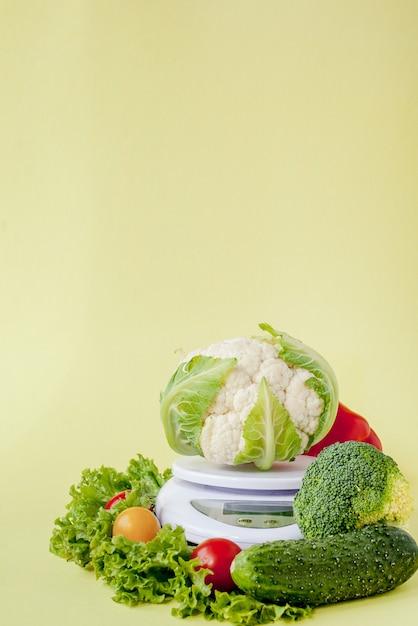 黄色の背景の花瓶に新鮮な野菜。健康的な食事、ダイエット計画、減量、デトックス、有機農業の概念。 Premium写真