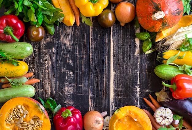 Fresh vegetables on a rustic dark textured table. autumn background Premium Photo