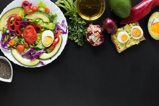 Fresh vegetables salad; toasted bread; fruits; oil over black background Free Photo