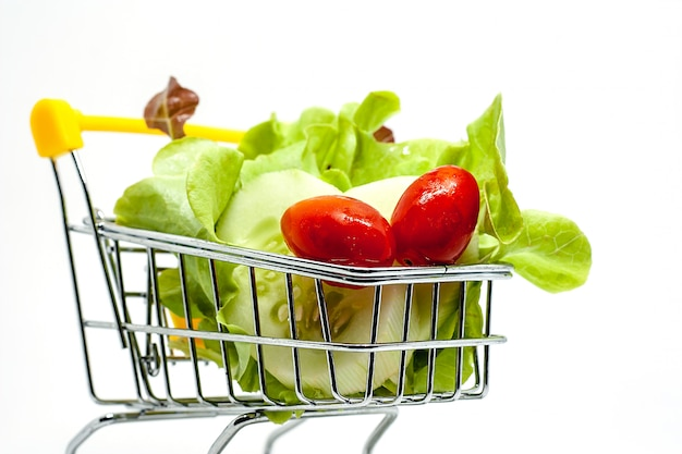 Fresh vegetables in the shopping cart on white background Premium Photo