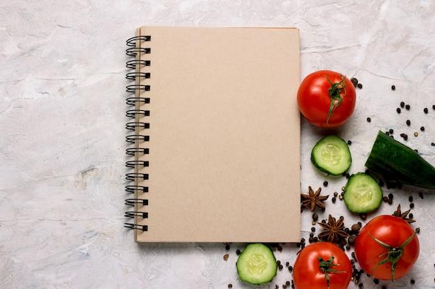新鮮な野菜、トマト、キュウリ、スパイス、明るい背景に食品レシピのメモ帳。 Premium写真