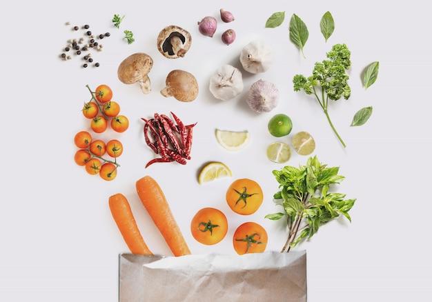 ハーブとスパイスが入った新鮮な野菜を買い物袋からこぼした Premium写真