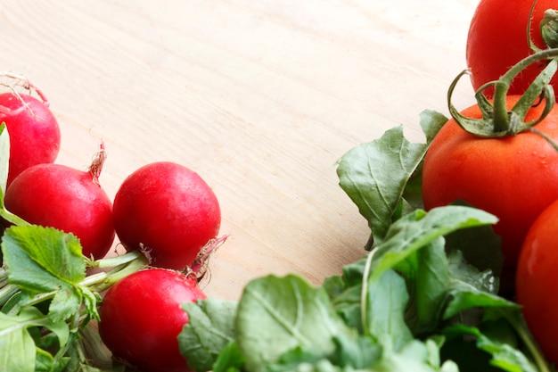 Fresh vegetables on a wooden board - radish, lettuce, arugula, tomatoes Premium Photo