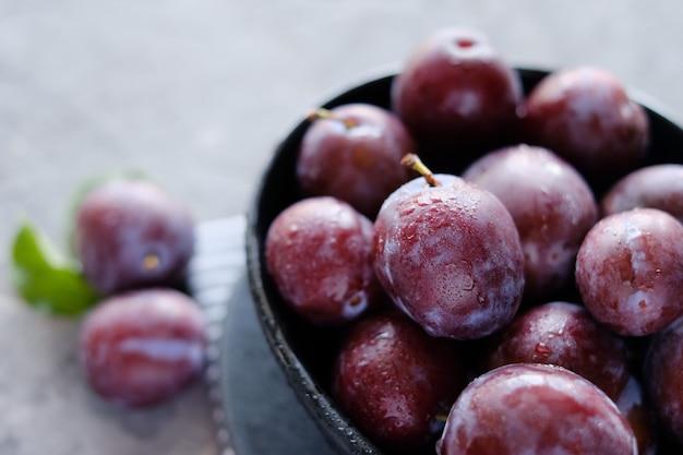 Fresh violet plums at dark gray table background Premium Photo