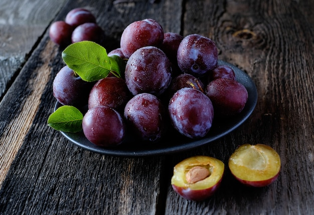 Fresh violet plums at dark wooden table background Premium Photo