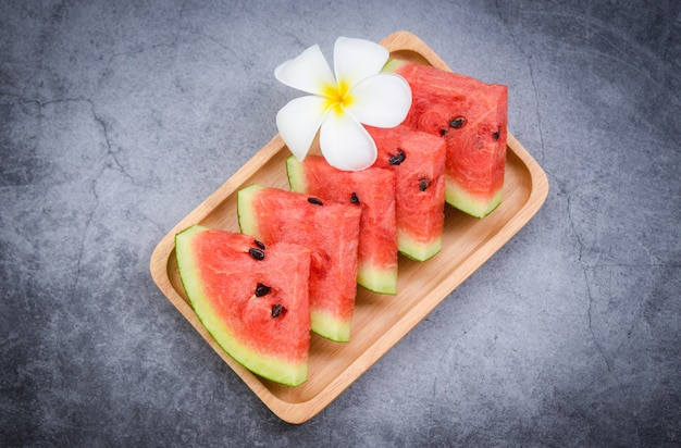 Fresh watermelon slice and white flower on black , watermelon tropical fruit on wood tray , selective focus Premium Photo