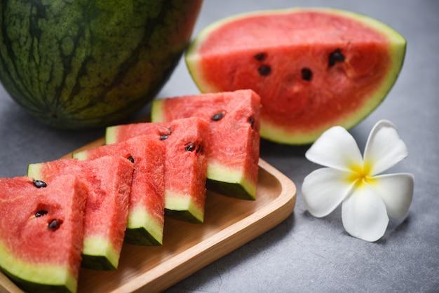 Fresh watermelon slice and white flower on concrete Premium Photo