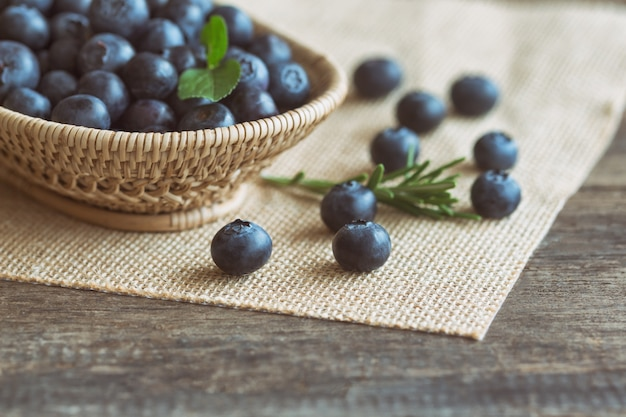 Fresh wild blueberries in wood basket on sack put on wooden table with copy space. Premium Photo