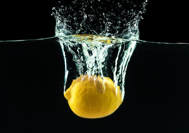 Fresh yellow lemon in water splash on black background Premium Photo