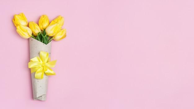 リボンとクラフト紙の新鮮な黄色のチューリップ。コピースペースと明るい春咲く花。 3月8日母の女性の日の背景。女性へのギフト。フラット横たわっていた。 Premium写真