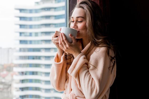 ピンクの柔らかいバスローブで新鮮な若い女性は、窓の外を見てお茶を飲みます。 無料写真