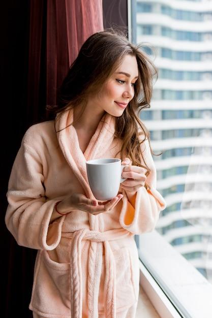 Giovane donna fresca in accappatoio rosa tenero beve il tè, guardando fuori dalla finestra. Foto Gratuite
