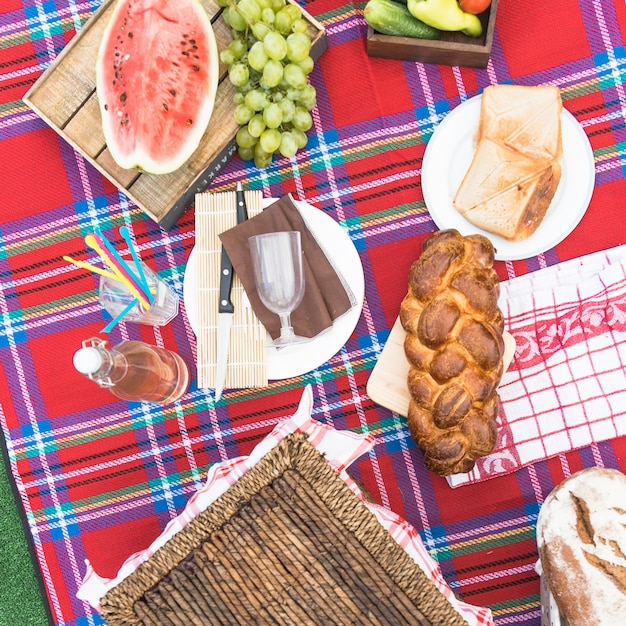 Freshly baked braided bread loaf; fruits and bread on checkered tablecloth Free Photo