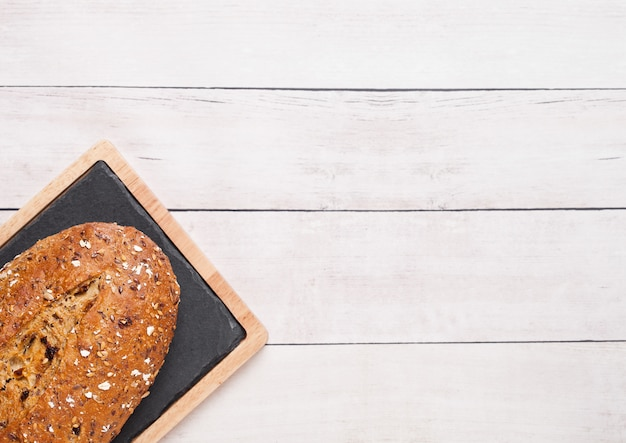 Freshly baked  bread with oats and kitchen towel on wooden board background Premium Photo