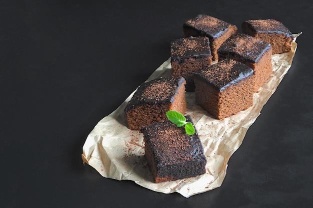 Свежеиспеченные классические пирожные на пергаменте выкладывают на черную поверхность Premium Фотографии