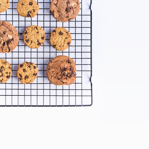 白い背景の上のオーブンネットで焼きたての自家製チョコレートチップクッキー 無料写真