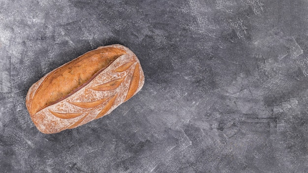 Freshly baked loaf of bread on black textured background Free Photo
