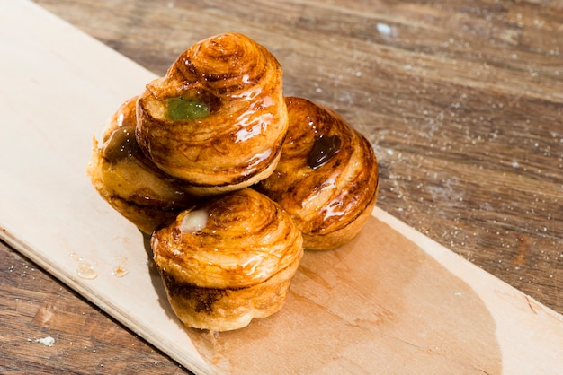Freshly baked sweet puff pastry on plank over the wooden desk Free Photo