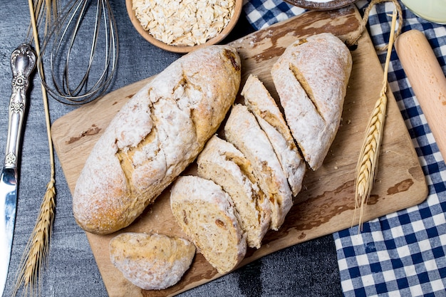 Freshly baked traditional bread on wooden table Oatmeal Bread Free Photo