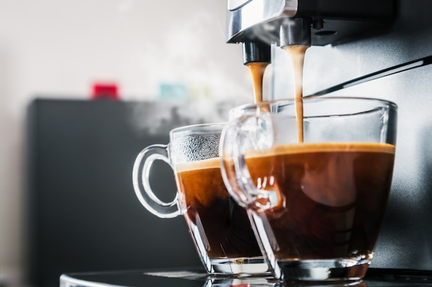 Freshly brewed coffee is poured from the coffee machine Premium Photo