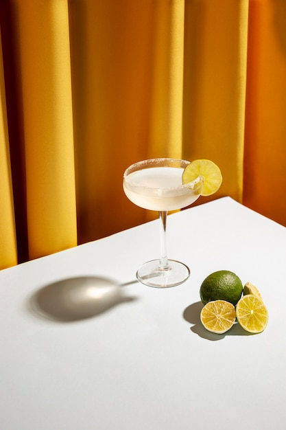 Freshly cocktail drink with salty rim and lemon slices over white desk Free Photo