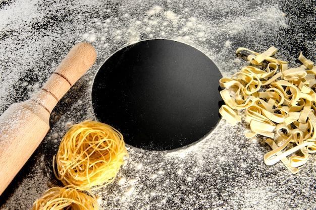Свежеприготовленные макароны лежат на темной поверхности, присыпанной мукой. ce. Premium Фотографии