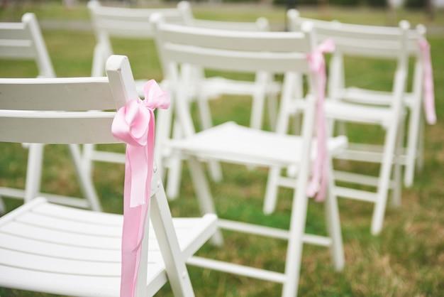 椅子に新鮮なカットの美しい赤と紫の結婚式の花の花輪。 無料写真