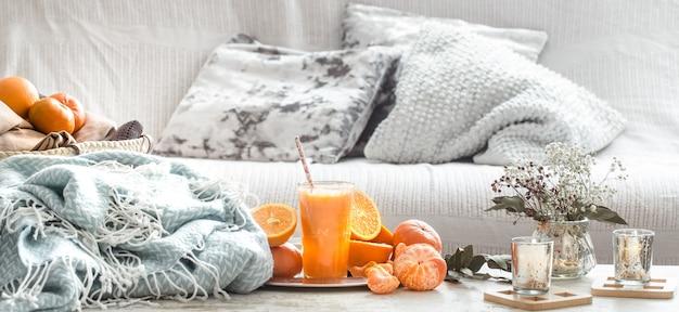Свежевыжатый органический свежий апельсиновый сок в интерьере дома, с бирюзовым одеялом и корзиной фруктов Бесплатные Фотографии