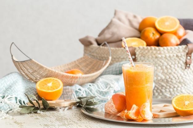 Succo d'arancia fresco biologico appena coltivato all'interno della casa, con una coperta turchese e un cesto di frutta. cibo salutare. vitamina c Foto Gratuite