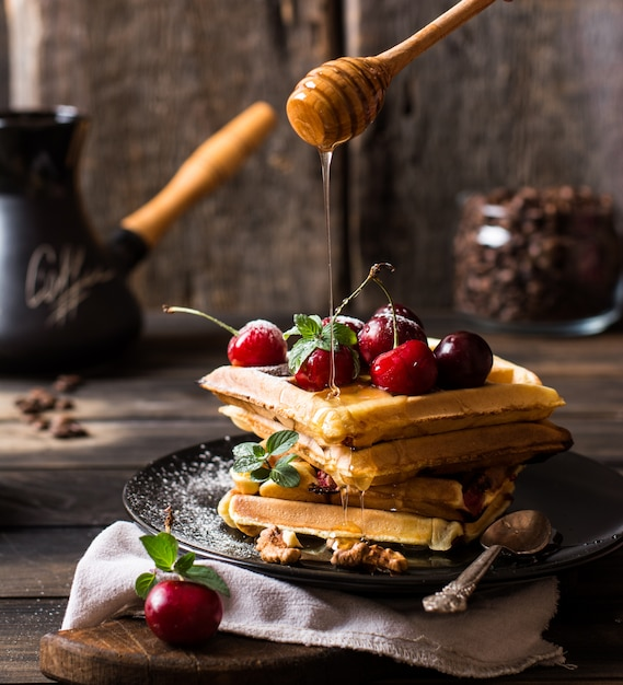 Freshly made belgian waffles with honey flows and powdered sugar. cherries on top of waffles on wooden desk and napkin on wooden background. coffee beans in glass jar. turkish coffee pot for breakfast Premium Photo