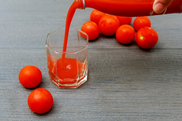 Freshly made tomato juice in a glass jug wooden board. Premium Photo