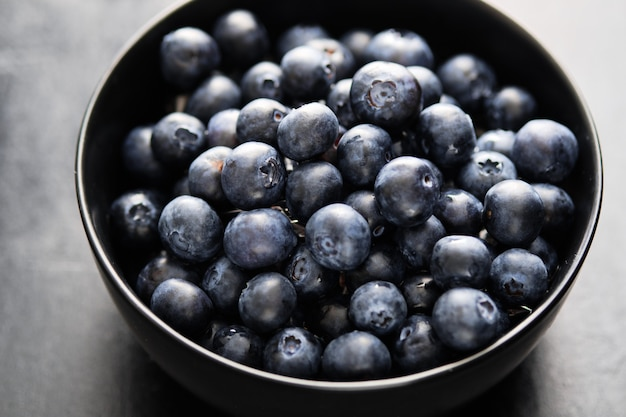 Freshly picked blueberries in black bowl on the table. Premium Photo