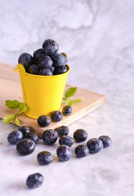 Freshly picked blueberries in yellow can Free Photo