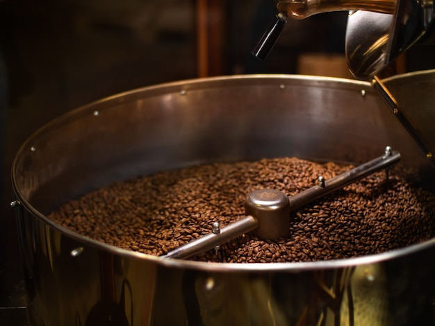 The freshly roasted coffee beans from a coffee roaster are mixing in the cooling cylinder Premium Photo