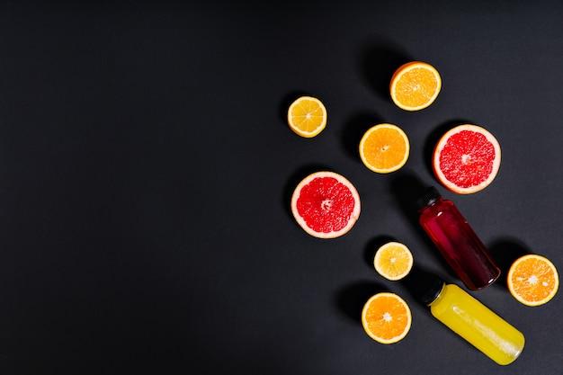 ボトルに入った絞りたての柑橘系ジュースは、壁にオレンジ、レモン、グレープフルーツの半分に囲まれています。 無料写真