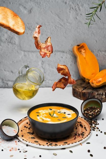 Жареные ломтики бекона, жареный хлеб, розмарин падают в миску с тыквенным супом Бесплатные Фотографии