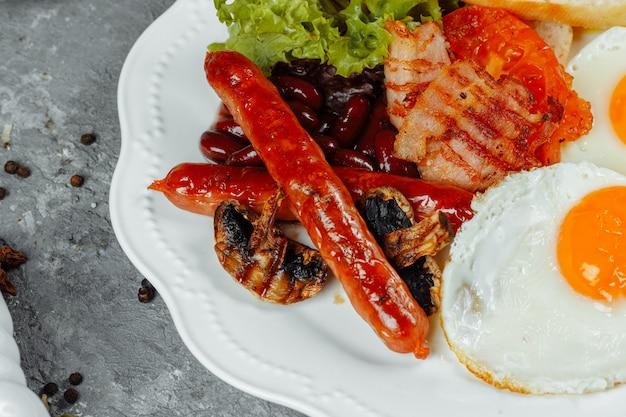 ベーコン、ソーセージ、ベイクドビーンズと一緒に揚げた朝食。 Premium写真
