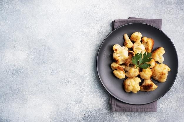 Fried cauliflower florets in batter on a black plate Premium Photo
