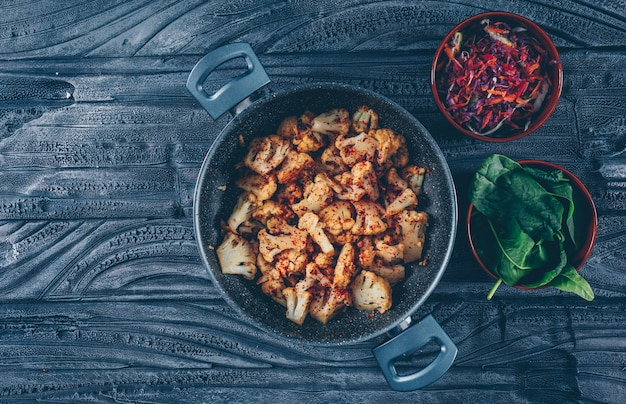 Fried cauliflower in a pot with vegetable salad, green top view on a dark wooden background. space for text Free Photo