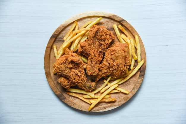 Fried chicken crispy on wooden tray with french fries on dining table background Premium Photo