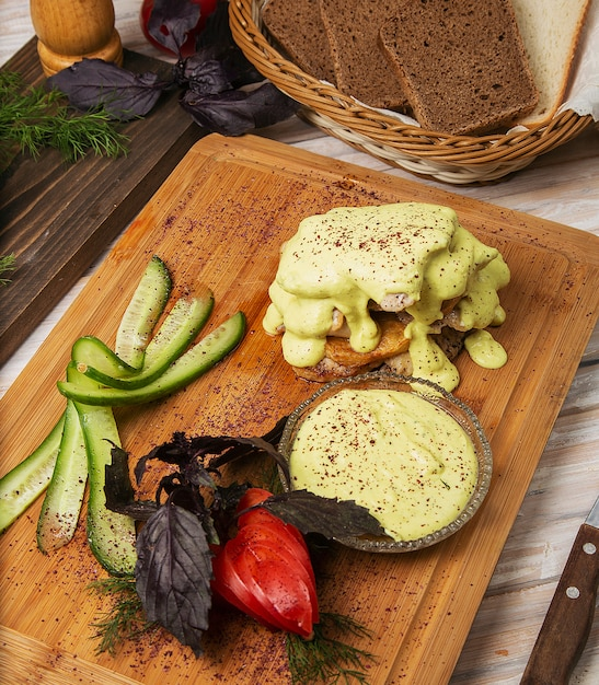 Fried chicken, fish fillet with melted cheese and tomato, cucumber salad on a wooden board Free Photo