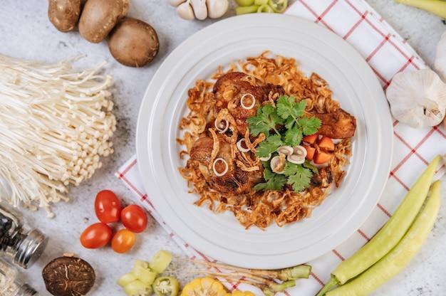 토마토, 칠리, 튀긴 양파, 양상추, 옥수수, 바늘 버섯을 곁들인 프라이드 치킨 다리. 무료 사진