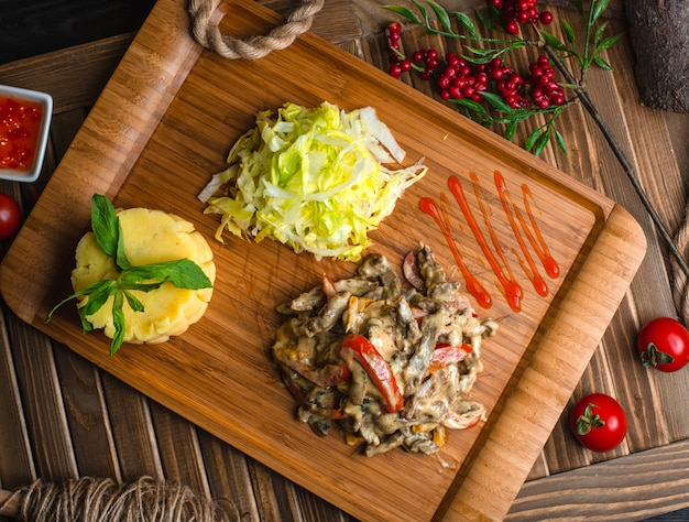 Fried chicken mushroom with vegetables on wooden board Free Photo