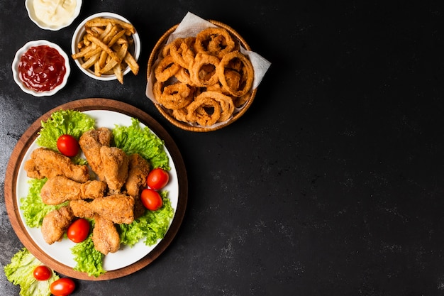 Fried chicken and onion rings with copy space Free Photo