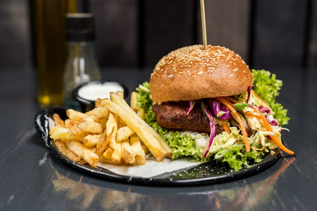 Fried chicken sandwich with vegetables and french fries on a wooden table Premium Photo