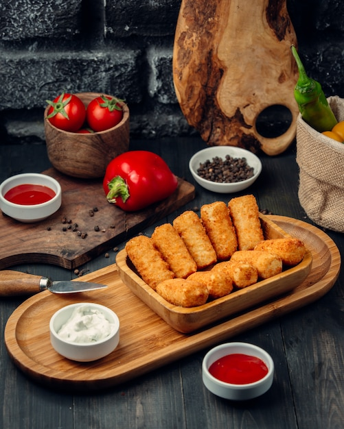 Fried chicken sticks on a wooden board with mayonnaise and tomato sauce. Free Photo