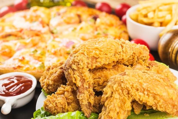 나무 테이블에 튀긴 닭 날개입니다. 무료 사진