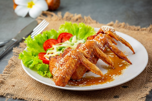 Fried chicken wings with fish sauce and sweet fish sauce. Free Photo